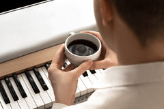 Il giovane uomo d'affari beve il caffè davanti al piano fotografia stock libera da diritti