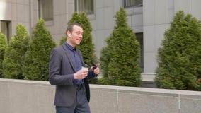 Il giovane uomo d'affari cammina con le cuffie senza fili ed aggressivamente conduce una discussione sulla telefonata stock footage