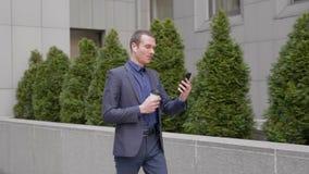 Il giovane uomo d'affari cammina con le cuffie senza fili in sue orecchie ed i colloqui sulla video conversazione sullo smartphon video d archivio