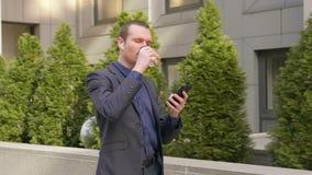 Il giovane uomo d'affari che cammina gi? la via con le cuffie senza fili nelle orecchie e scrive un messaggio sul telefono video d archivio