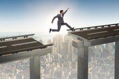 Il giovane uomo d'affari che salta sopra il ponte Fotografie Stock Libere da Diritti