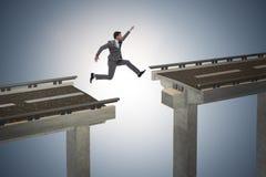 Il giovane uomo d'affari che salta sopra il ponte Fotografia Stock