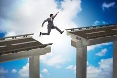 Il giovane uomo d'affari che salta sopra il ponte Immagini Stock