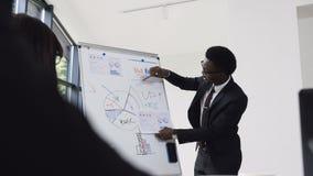 Il giovane uomo d'affari conduce la presentazione facendo uso della lavagna su cui mostra i grafici comprare e la società di vend video d archivio