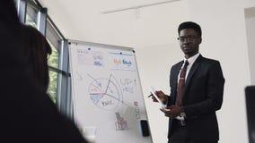 Il giovane uomo d'affari conduce la presentazione facendo uso della lavagna su cui mostra i grafici comprare e la società di vend stock footage