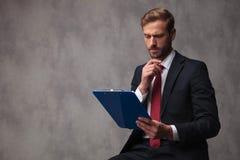 Il giovane uomo d'affari confuso sta leggendo i dati sulla lavagna per appunti e sottile fotografia stock