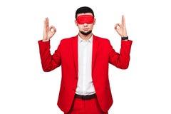 Il giovane uomo d'affari conta su fortuna, fortuna uomo barbuto in un vestito rosso con una benda rossa immagini stock