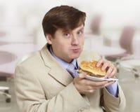Il giovane uomo d'affari divertente mangia un hamburger Fotografia Stock