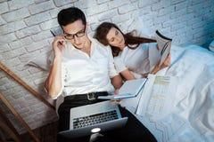 Il giovane uomo d'affari esamina lo schermo del computer portatile L'uomo fa le note in taccuino nero immagine stock libera da diritti