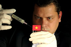 Il giovane uomo d'affari fa un'iniezione finanziaria alla bandiera vietnamita Fotografia Stock