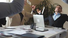 Il giovane uomo d'affari getta sul pacco di soldi che hanno emozioni allegre I riusciti uomini d'affari celebrano l'innalzamento  video d archivio