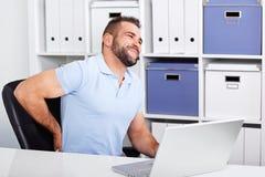 Il giovane uomo d'affari ha mal di schiena sul lavoro con un computer portatile Fotografie Stock