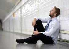 Il giovane uomo d'affari ha perso nella depressione che si siede sul sottopassaggio a terra della via Fotografia Stock