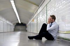 Il giovane uomo d'affari ha perso nella depressione che si siede sul sottopassaggio a terra della via Fotografia Stock Libera da Diritti