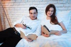 Il giovane uomo d'affari legge il libro a letto con la sua moglie Le coppie stanno trovando a letto a casa fotografie stock libere da diritti
