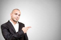 Il giovane uomo d'affari mostra qualcosa con la sua mano Fotografia Stock