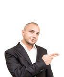 Il giovane uomo d'affari mostra qualcosa con la sua mano Fotografie Stock Libere da Diritti