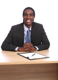 Il giovane uomo d'affari nero felice si siede alla scrivania fotografie stock