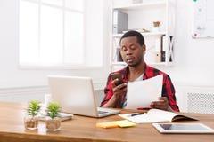 Il giovane uomo d'affari nero ha letto i documenti e mandare un sms sul cellulare in ufficio bianco moderno fotografie stock