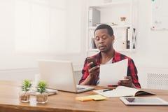 Il giovane uomo d'affari nero ha letto i documenti e mandare un sms sul cellulare in ufficio bianco moderno immagini stock