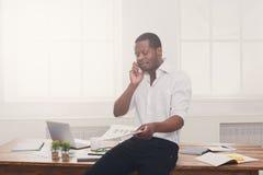 Il giovane uomo d'affari nero ha letto i documenti e parla sul cellulare in ufficio bianco moderno fotografia stock
