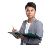 Il giovane uomo d'affari scrive sulla lavagna per appunti Fotografia Stock