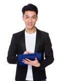 Il giovane uomo d'affari scrive sulla lavagna per appunti Fotografie Stock