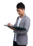 Il giovane uomo d'affari scrive sulla lavagna per appunti Immagini Stock Libere da Diritti