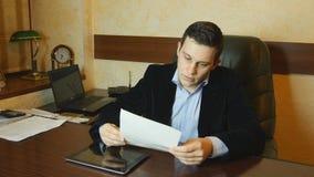 Il giovane uomo d'affari serio che guarda il rapporto in ufficio ed analizza il documento stock footage