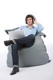Il giovane uomo d'affari si distende con musica ed il computer portatile Immagini Stock