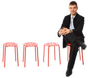 Il giovane uomo d'affari si siede sul piedino rosso delle feci sul piedino Immagine Stock