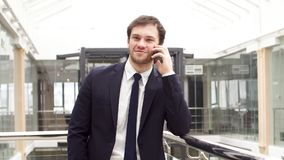 Il giovane uomo d'affari sicuro è negoziazione corporativa allo smartphone in ingresso dell'ufficio moderno archivi video