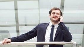 Il giovane uomo d'affari sicuro ? negoziazione corporativa allo smartphone in ingresso dell'ufficio moderno video d archivio
