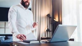 Il giovane uomo d'affari sorridente barbuto in camicia bianca è scrittorio vicino diritto davanti al computer portatile, tenuta n immagini stock libere da diritti