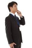 Il giovane uomo d'affari sta comunicando su un telefono mobile Immagini Stock
