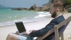 Il giovane uomo d'affari sta lavorando al computer portatile sulla spiaggia stock footage