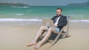 Il giovane uomo d'affari sta lavorando il suo computer portatile sulla spiaggia tropicale video d archivio