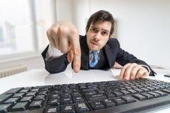 Il giovane uomo d'affari sta premendo fornisce la chiave sulla tastiera e sulla presentazione della forma Fotografie Stock