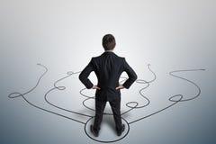 Il giovane uomo d'affari sta prendendo la decisione e sta selezionando la strategia Vista da dietro immagini stock
