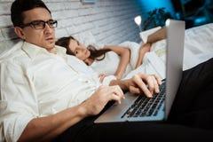 Il giovane uomo d'affari sta scrivendo sul computer portatile in camera da letto La donna è libro di lettura che si trova a letto immagini stock