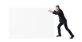 Il giovane uomo d'affari sta spingendo via una grande insegna in bianco su fondo bianco Fotografie Stock
