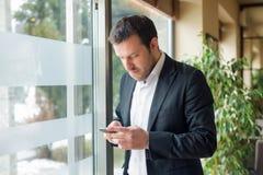 Il giovane uomo d'affari sta stando accanto alla finestra fotografie stock libere da diritti