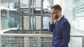 Il giovane uomo d'affari utilizza lo smartphone, stante nel centro di affari stock footage