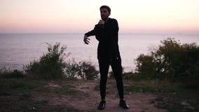 Il giovane uomo del brunettte nel vestito nero di sport che fa il riscaldamento, allunga le sue armi mentre sta sull'erba Bella s stock footage