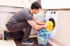 Il giovane uomo del marito che fa lavanderia a casa immagini stock libere da diritti