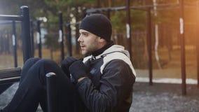 Il giovane uomo dell'atleta che fa l'esercizio sui abdominals muscles alla palestra all'aperto nel parco dell'inverno Immagine Stock