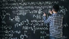 Il giovane uomo dello scienziato scrive il cuneo in chimico e le equazioni matematiche murano l'interno della stanza Fotografia Stock