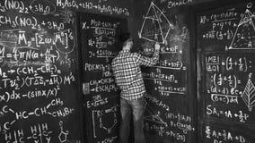 Il giovane uomo dello scienziato scrive il cuneo in chimico e le equazioni matematiche murano l'interno della stanza Fotografia Stock Libera da Diritti