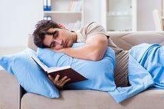 Il giovane uomo dello studente che prepara per gli esami dell'istituto universitario a letto con il libro Immagini Stock