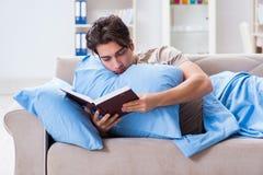 Il giovane uomo dello studente che prepara per gli esami dell'istituto universitario a letto con il libro Fotografie Stock